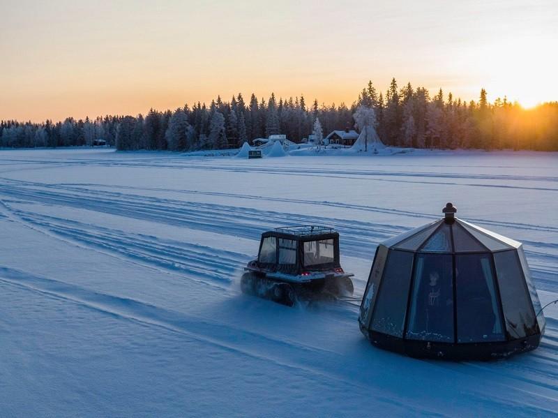 AuroraHut lasi-iglu tinkerin vedettävänä talvella 2020 Ranuanjärven jäällä. Arctic Guesthouse & Igloos