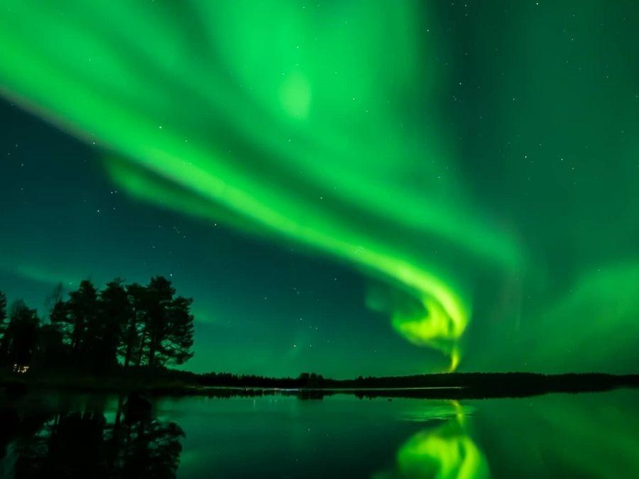 Aurora borealis aka northern lights on top of a lake in Finnish Lapland