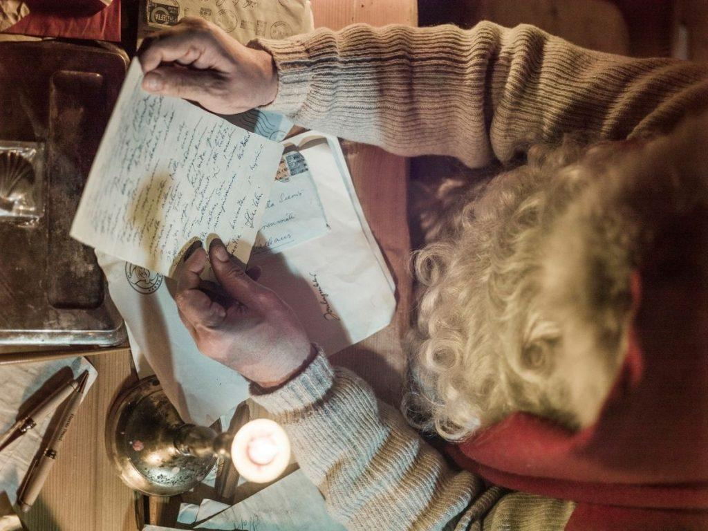 Santa Claus is reading a letter that he has received from abroad